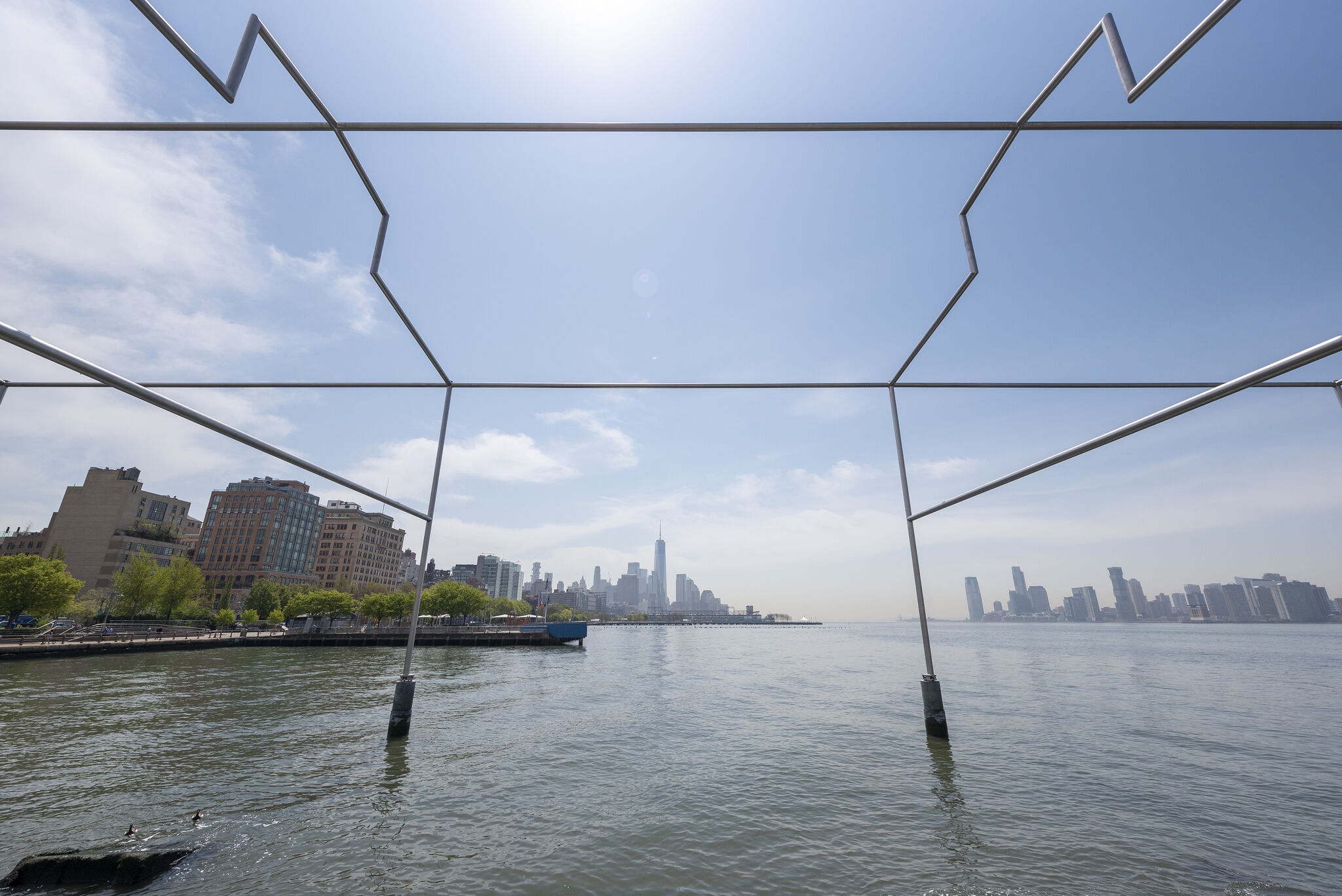 Close-up view of Day's End metal sculpture, with the steel beams framing the New York and New Jersey skylines against the horizon of the Hudson River.