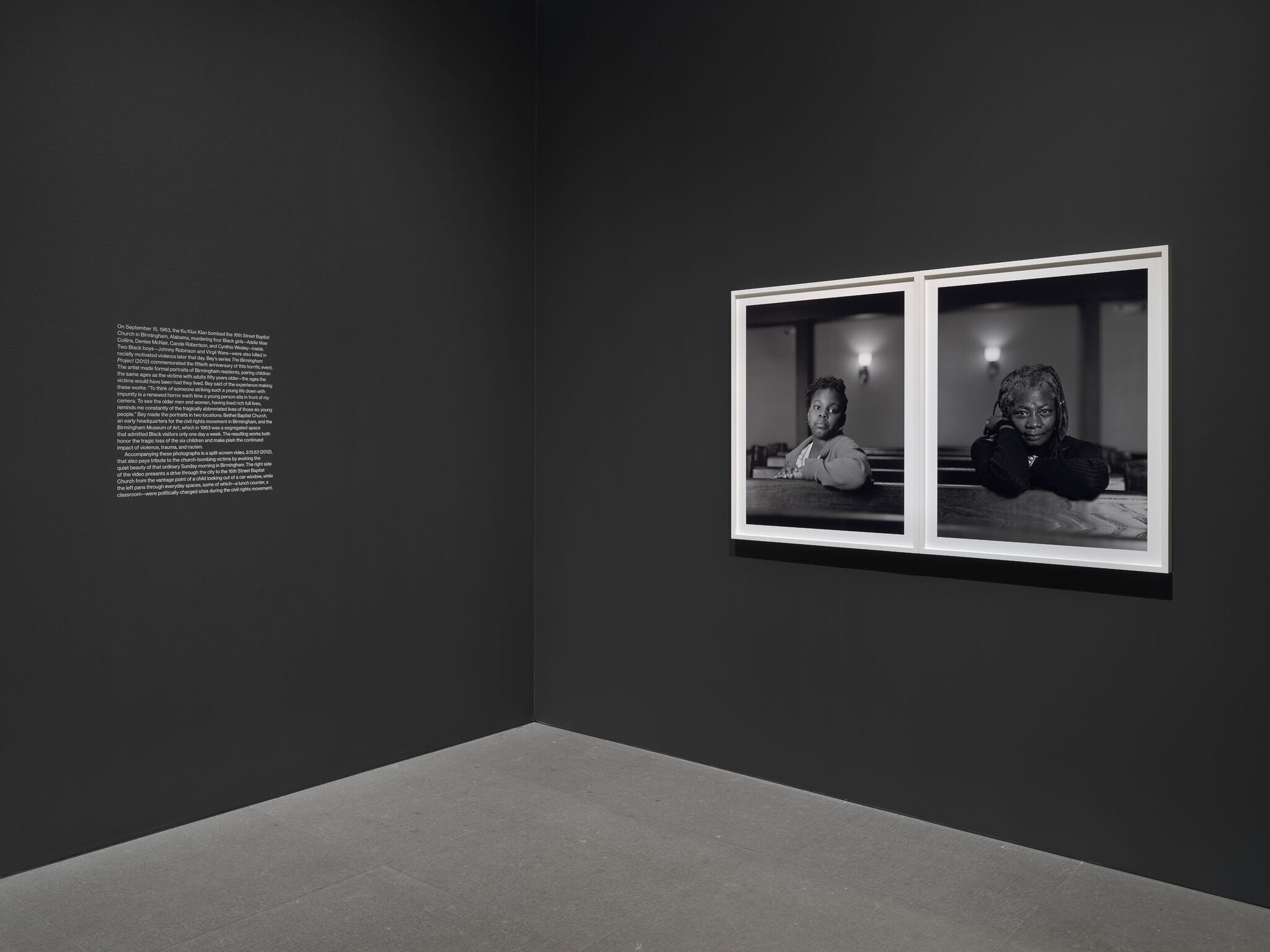 A corner of a main exhibition room with a text vinyl on one adjoining wall and a diptych piece from the Dawoud Bey exhibition on the other.