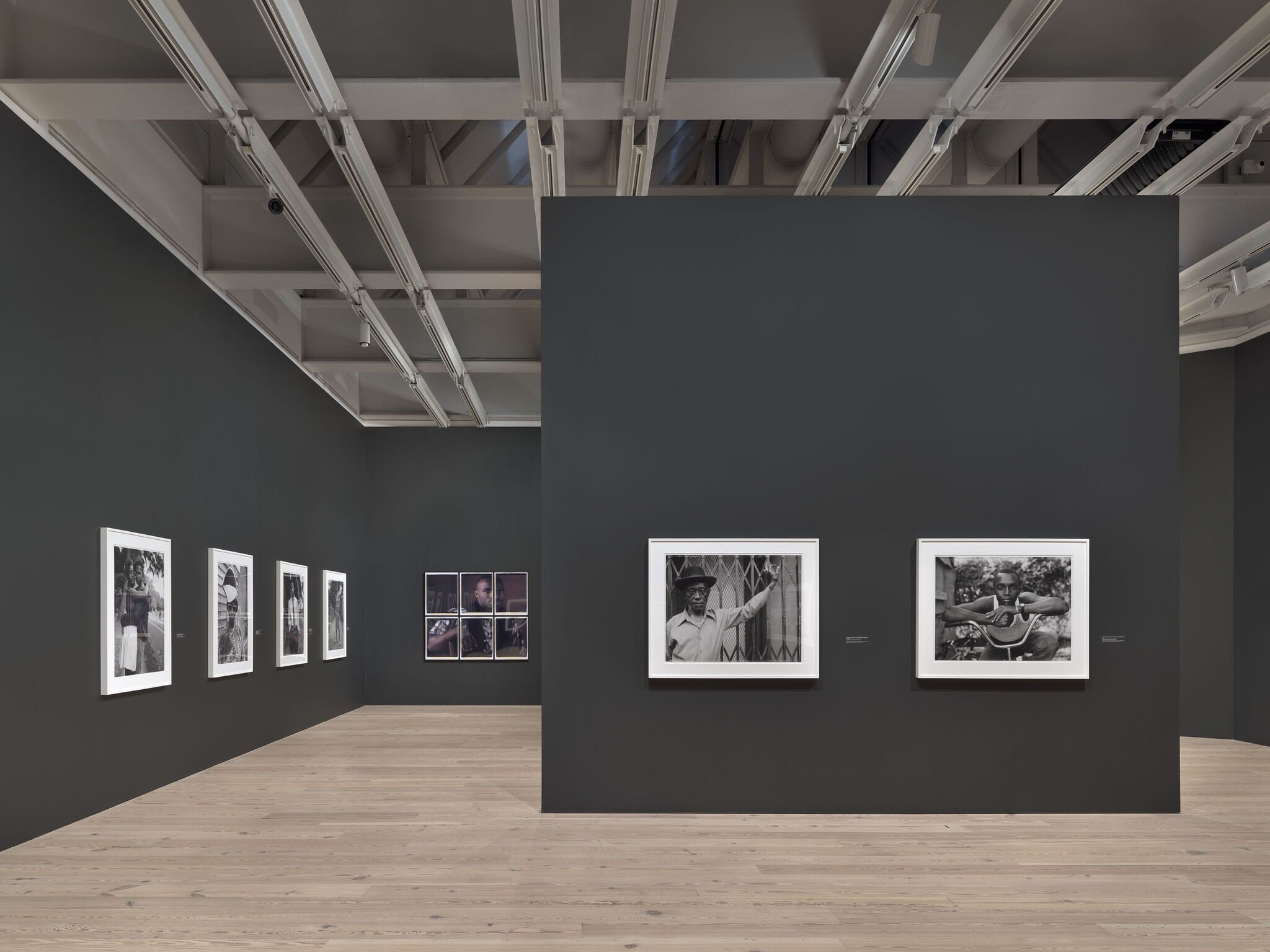 A main exhibition room of the Whitney with pieces mounted against black walls.