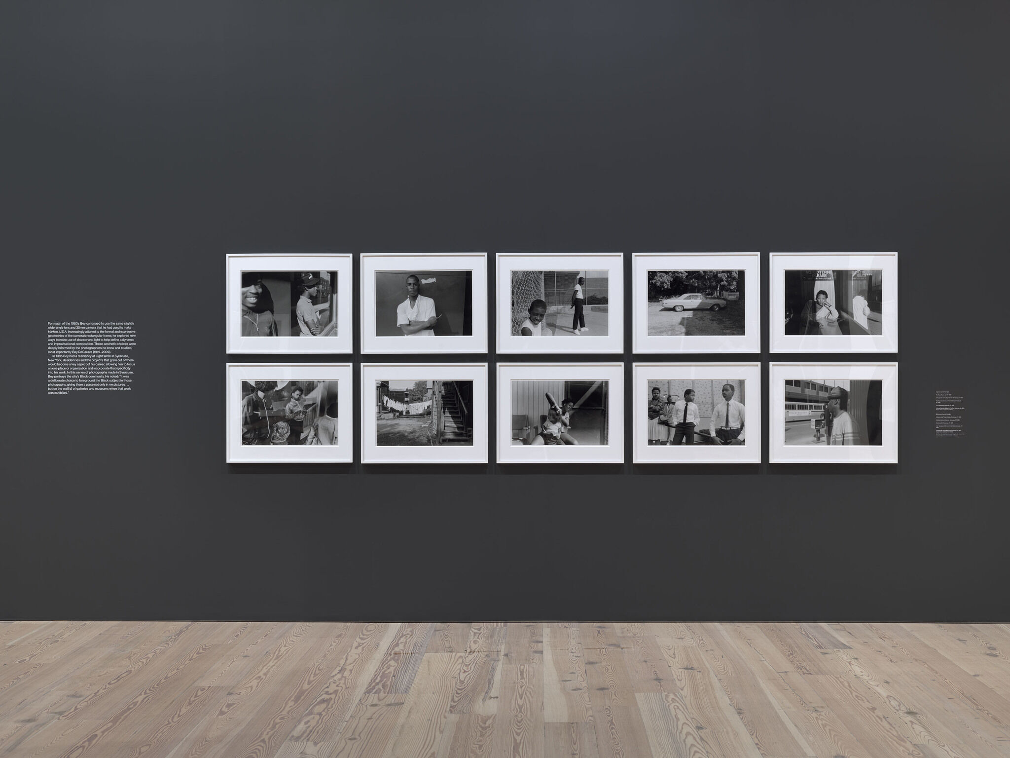 Ten framed photographs from the Dawoud Bey exhibition mounted against a black wall.