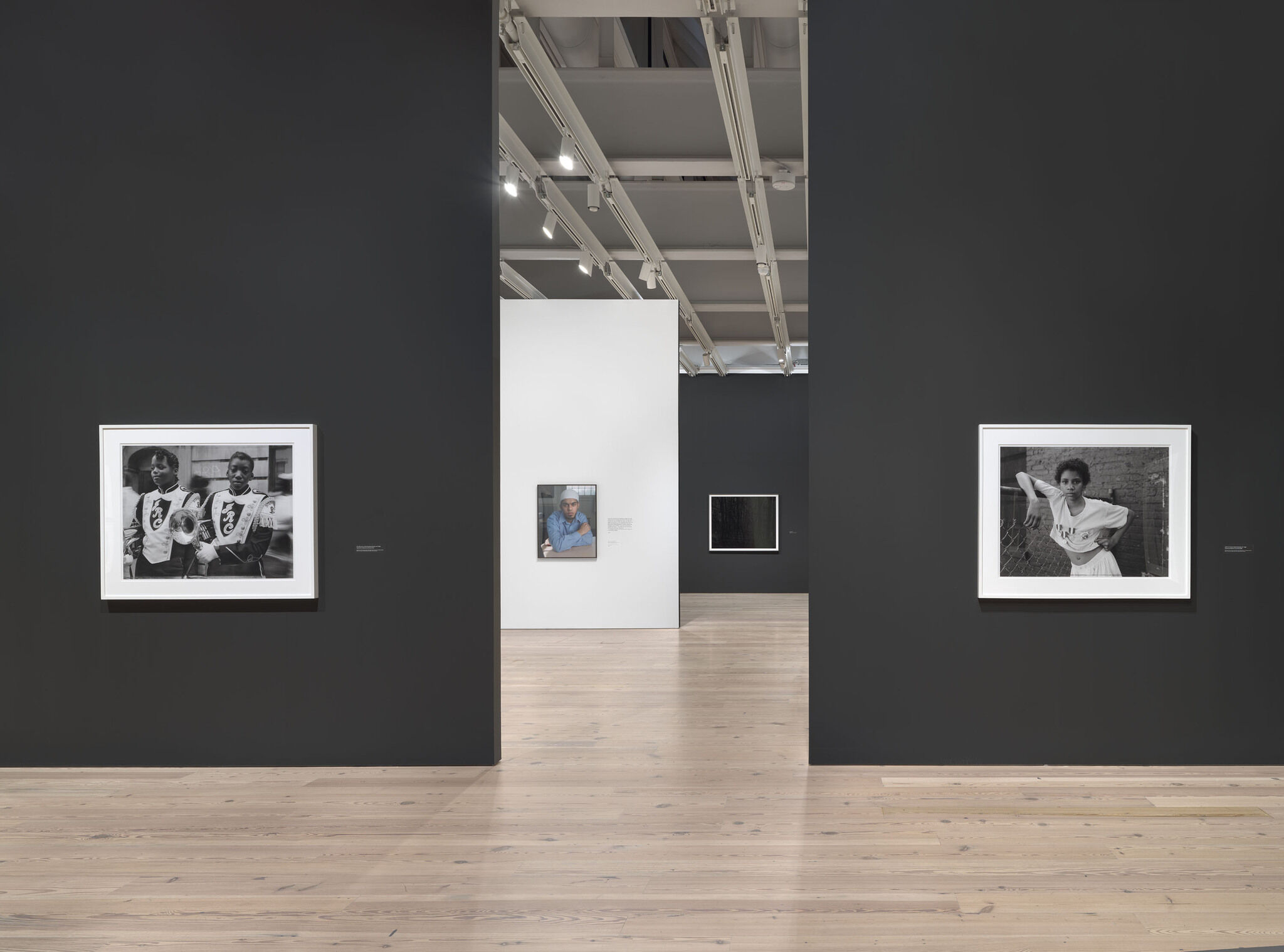 A main exhibition room of the Whitney with pieces mounted against black and white walls.