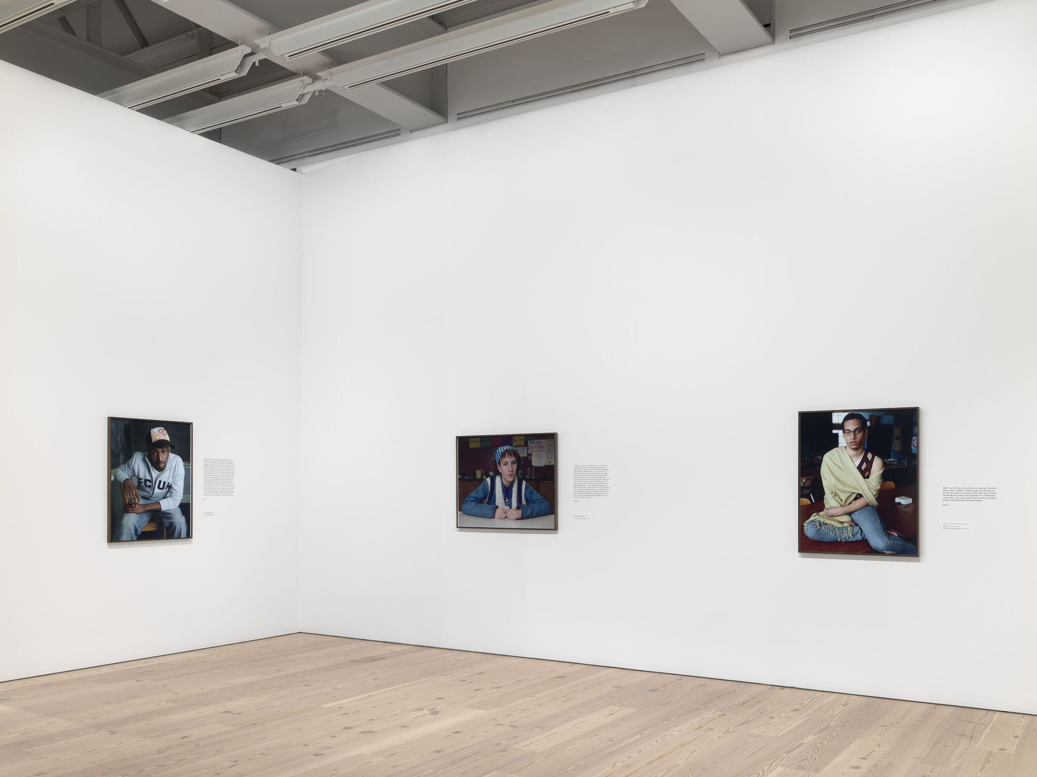 A corner of a main exhibition room with pieces from the Dawoud Bey exhibition mounted against white walls.