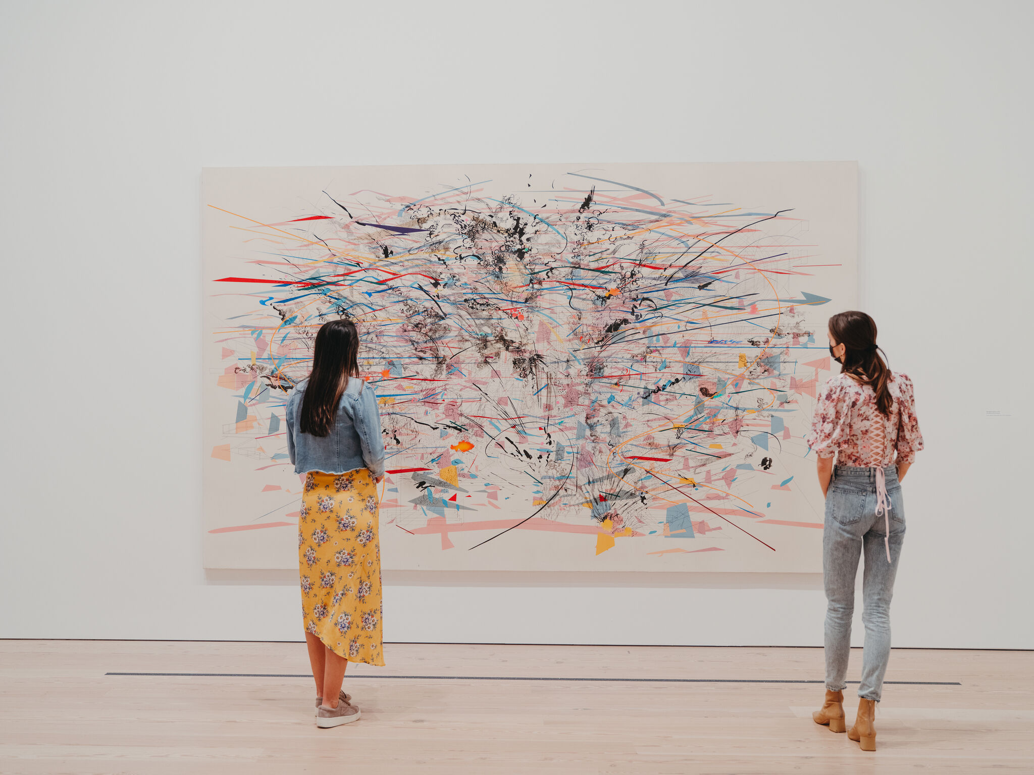 Two masked visitors stand in front of and view a colorful abstract painting hanging on a white wall.