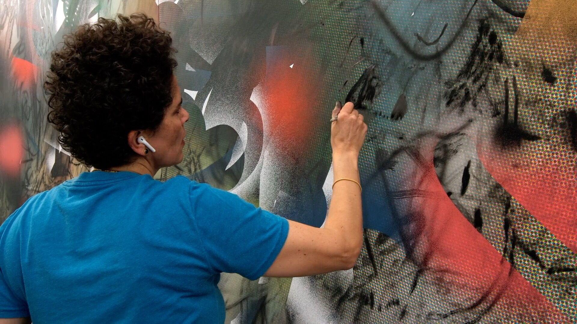 The artist Julie Mehretu painting one of her works.