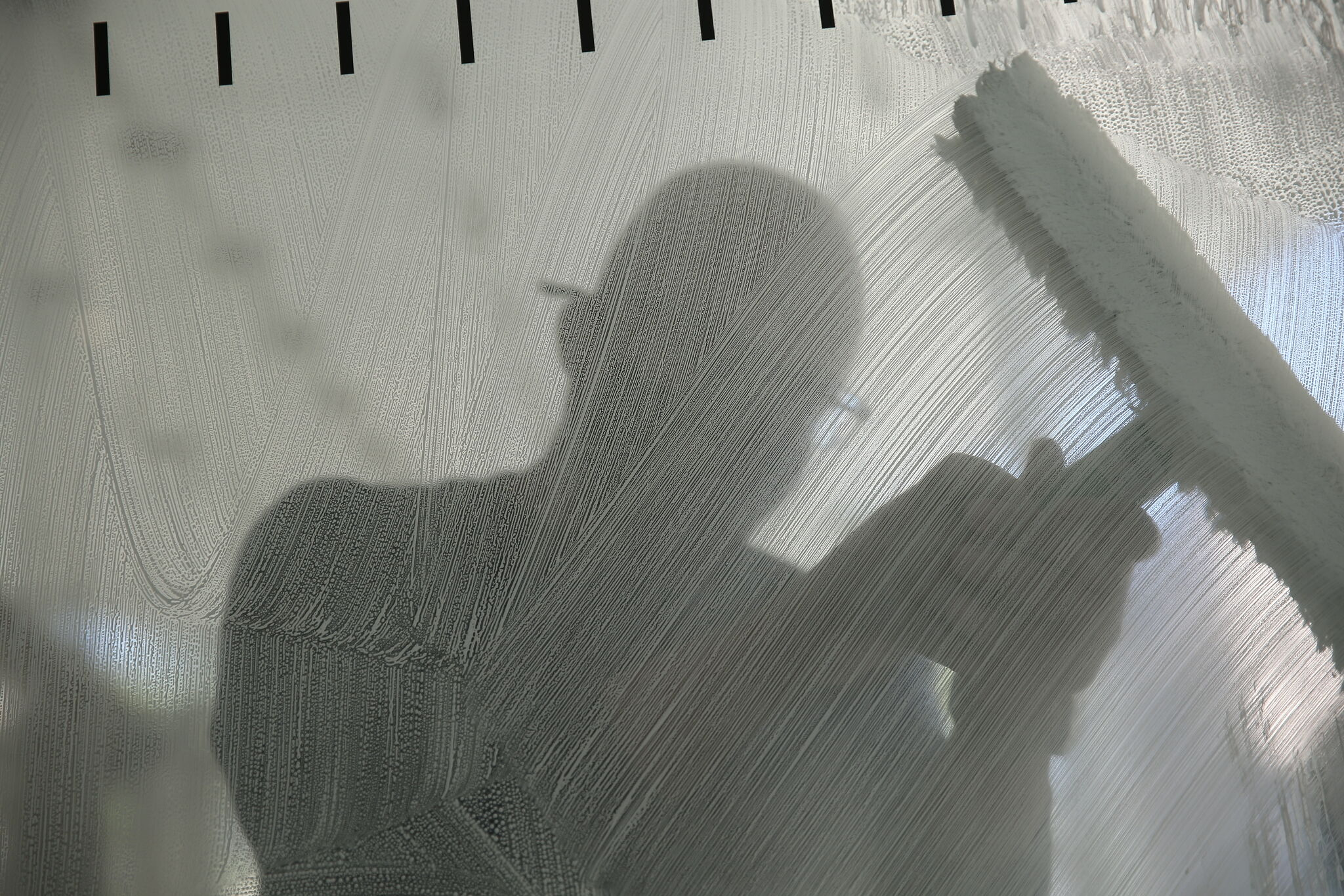 A person cleaning a glass window with a window wiper.