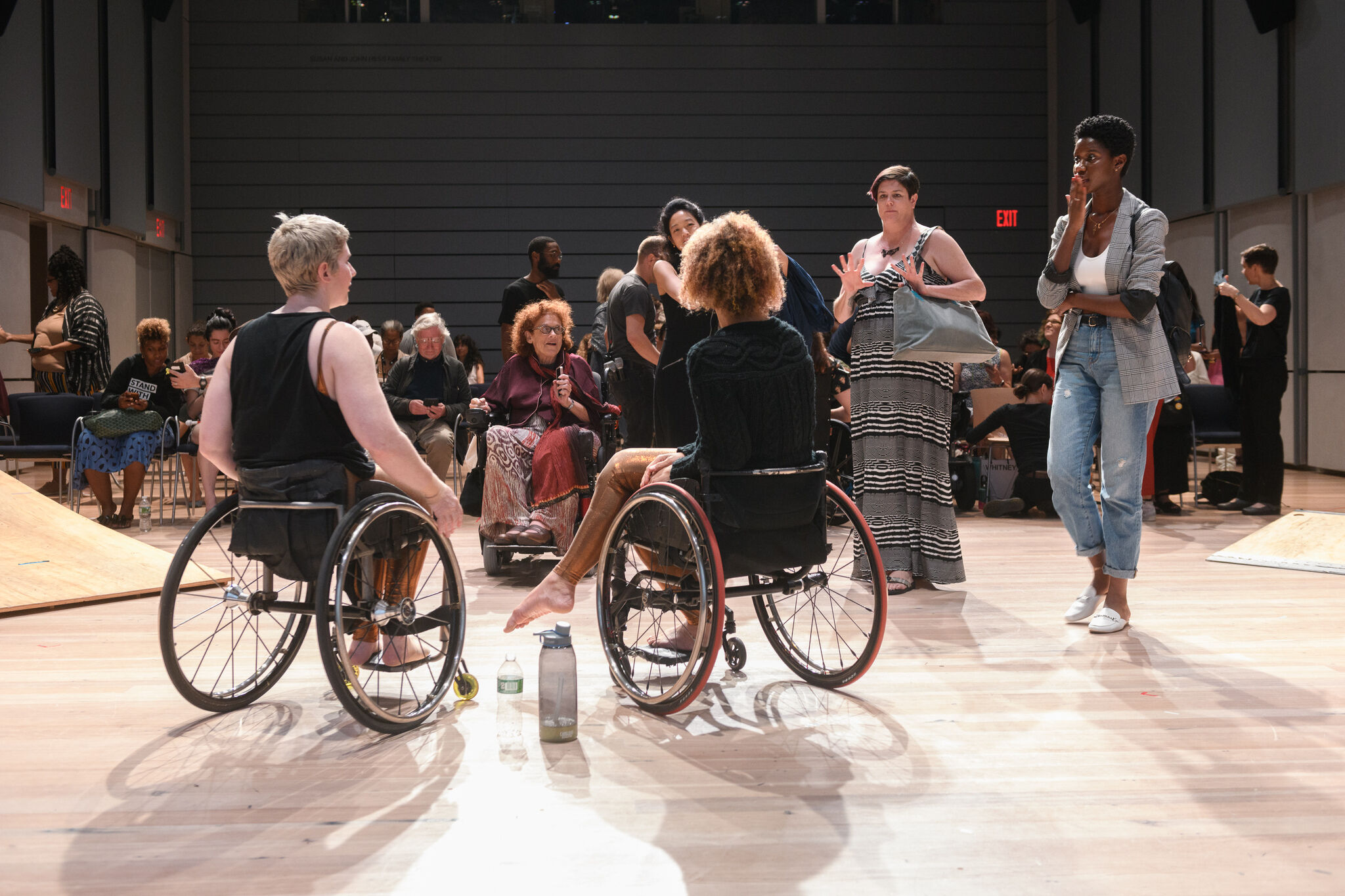 Two people in wheelchairs face away from the camera, engaged in a conversation with audience members gesturing.