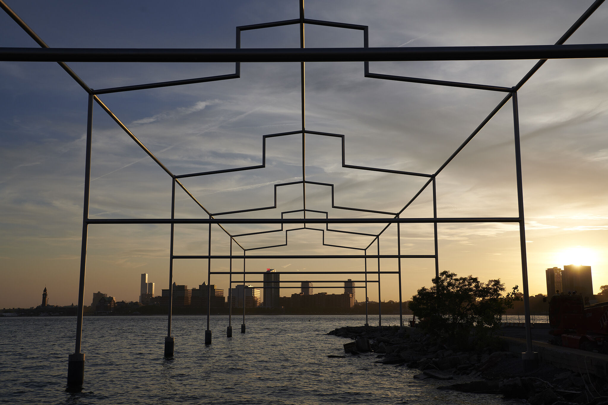 Close-up frontal view of Day's End steel sculpture, with sunset and New Jersey skyline in the background.