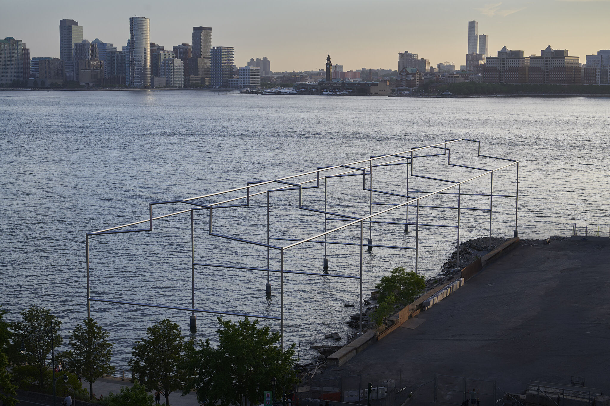 Overhead view of Day's End steel sculpture on the Hudson river at sunset, with New Jersey skyline in the background.