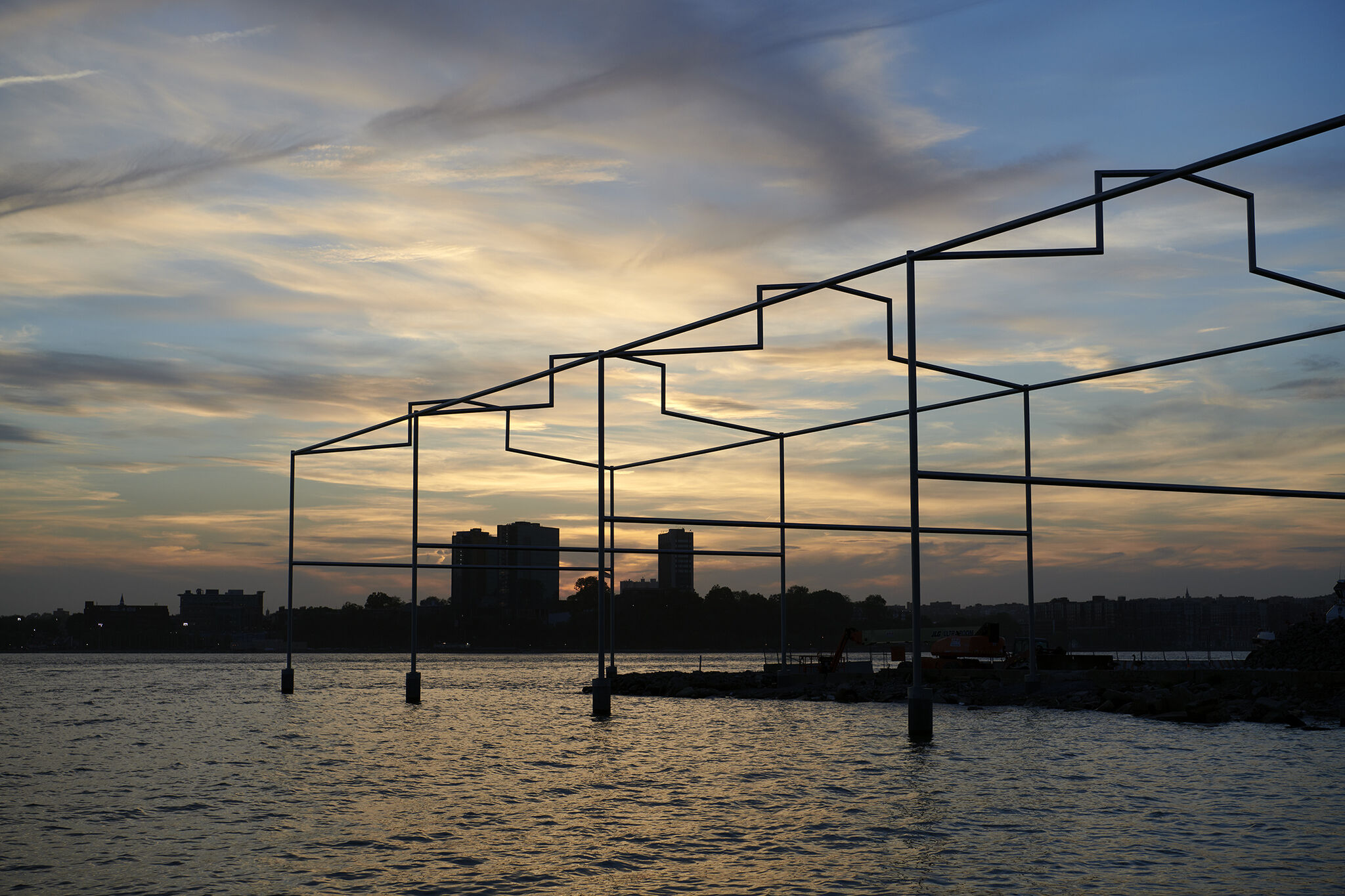 Day's End steel sculpture on the Hudson River, with sunset and New Jersey skyline in the background.