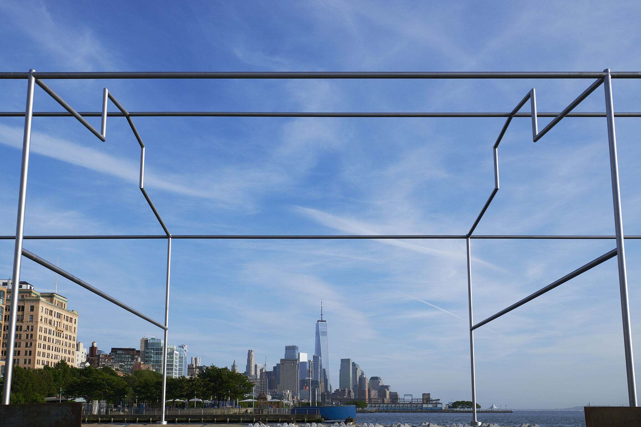 Close-up view of Day's End steel sculpture framing the Manhattan skyline in the background.