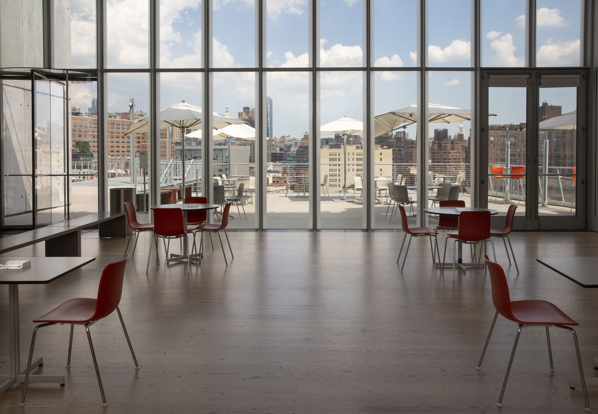 Open, interior dining space with tables and chair symmetrically arranged, looking out through floor-to-ceiling glass windows onto an open terrace space.