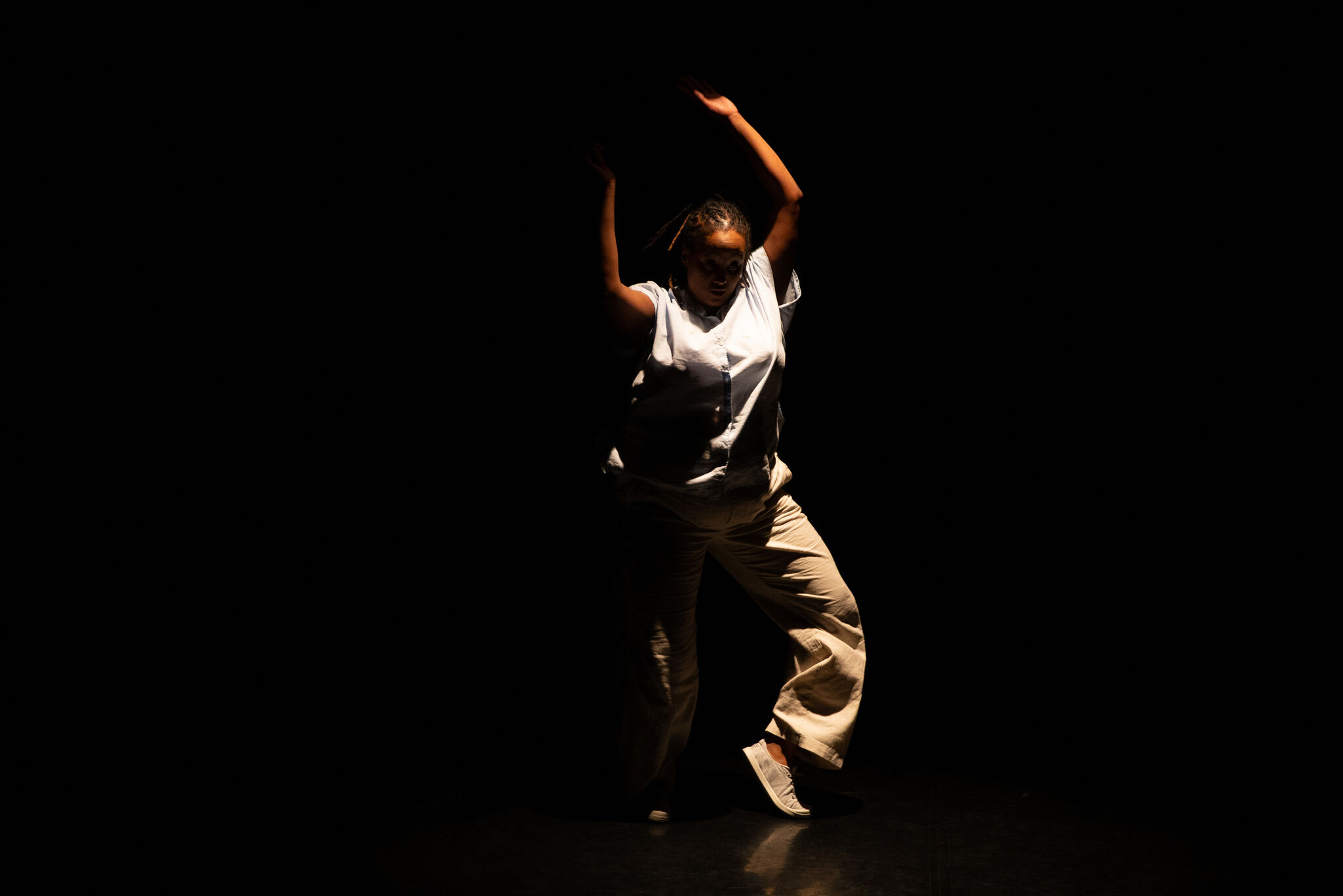 A Black person dances in narrow shaft of light, surrounded by darkness. They wear a light blue button-down, tan pants and white sneakers.