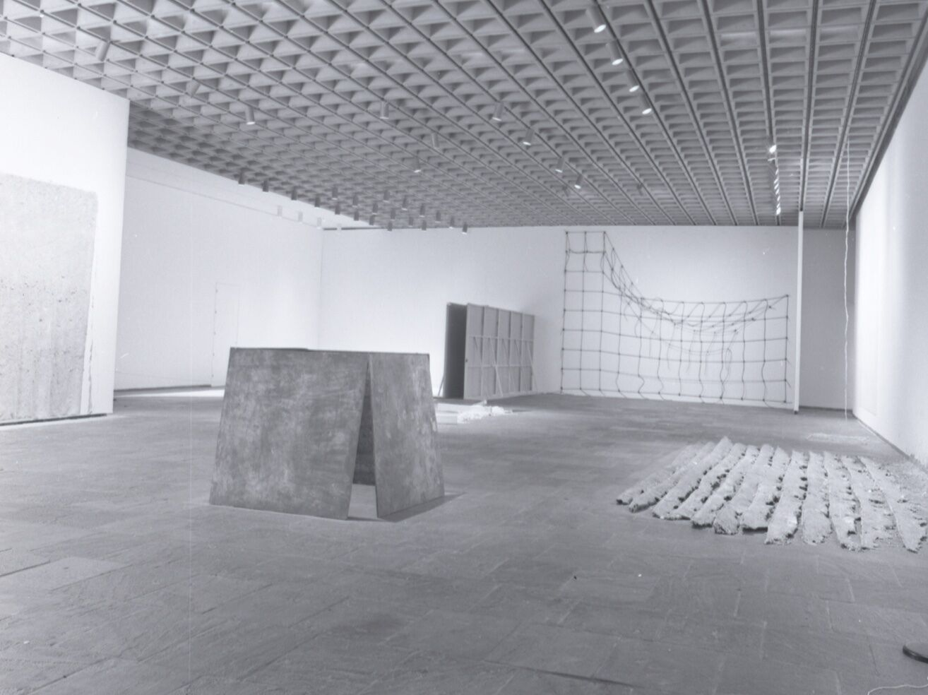 A grayscale image of a large exhibition room with a few pieces situated on the floor.
