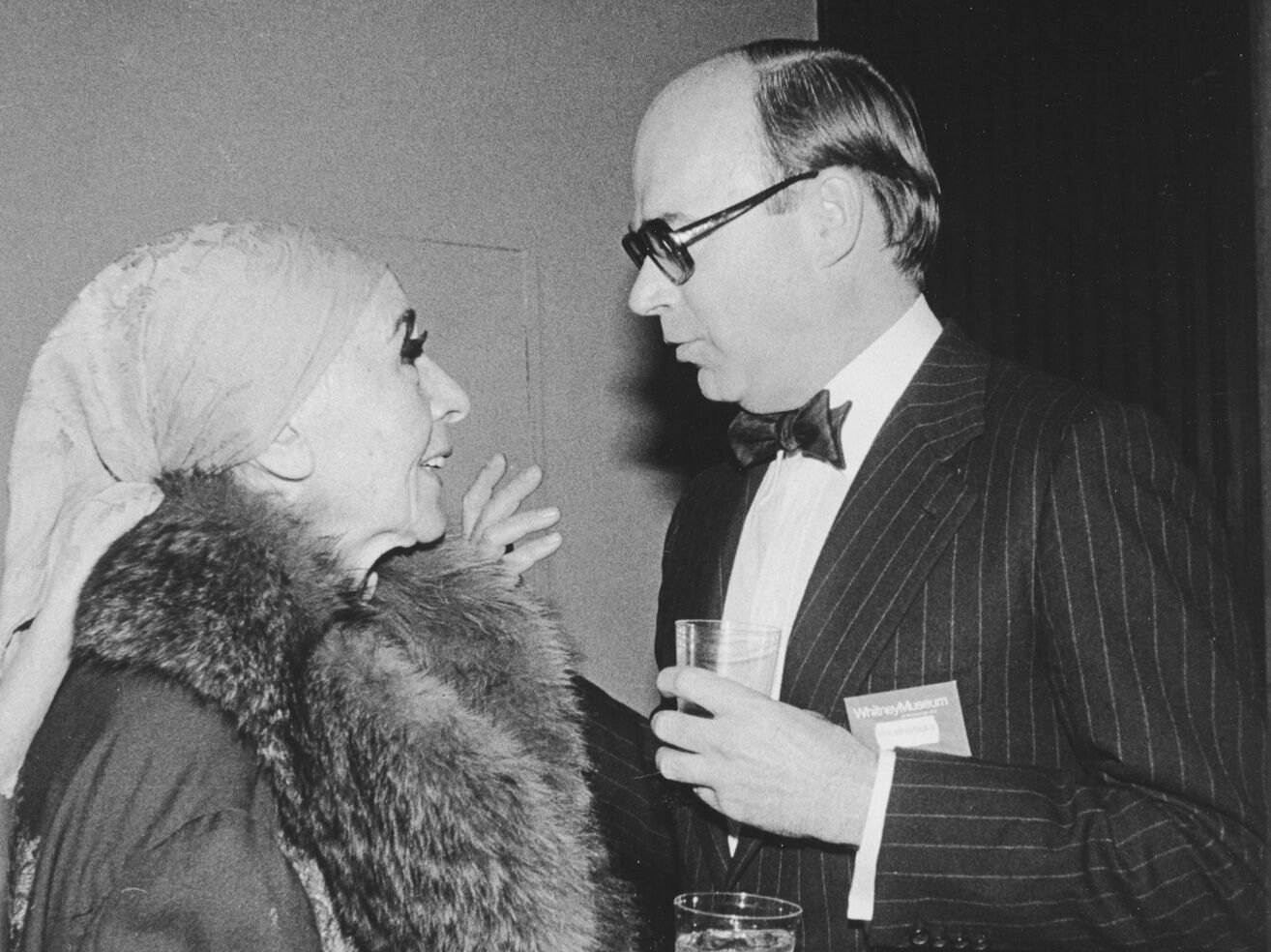 Two people, dressed formally, are in the middle of a conversation.
