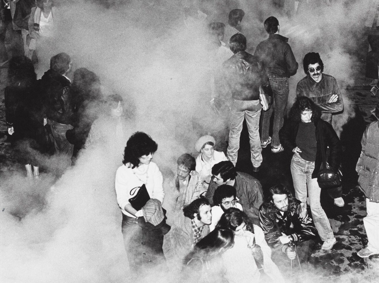 A group of people are standing outside surrounded by smoke.