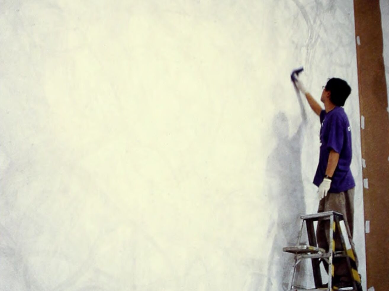 A person on a ladder painting on a large wall.