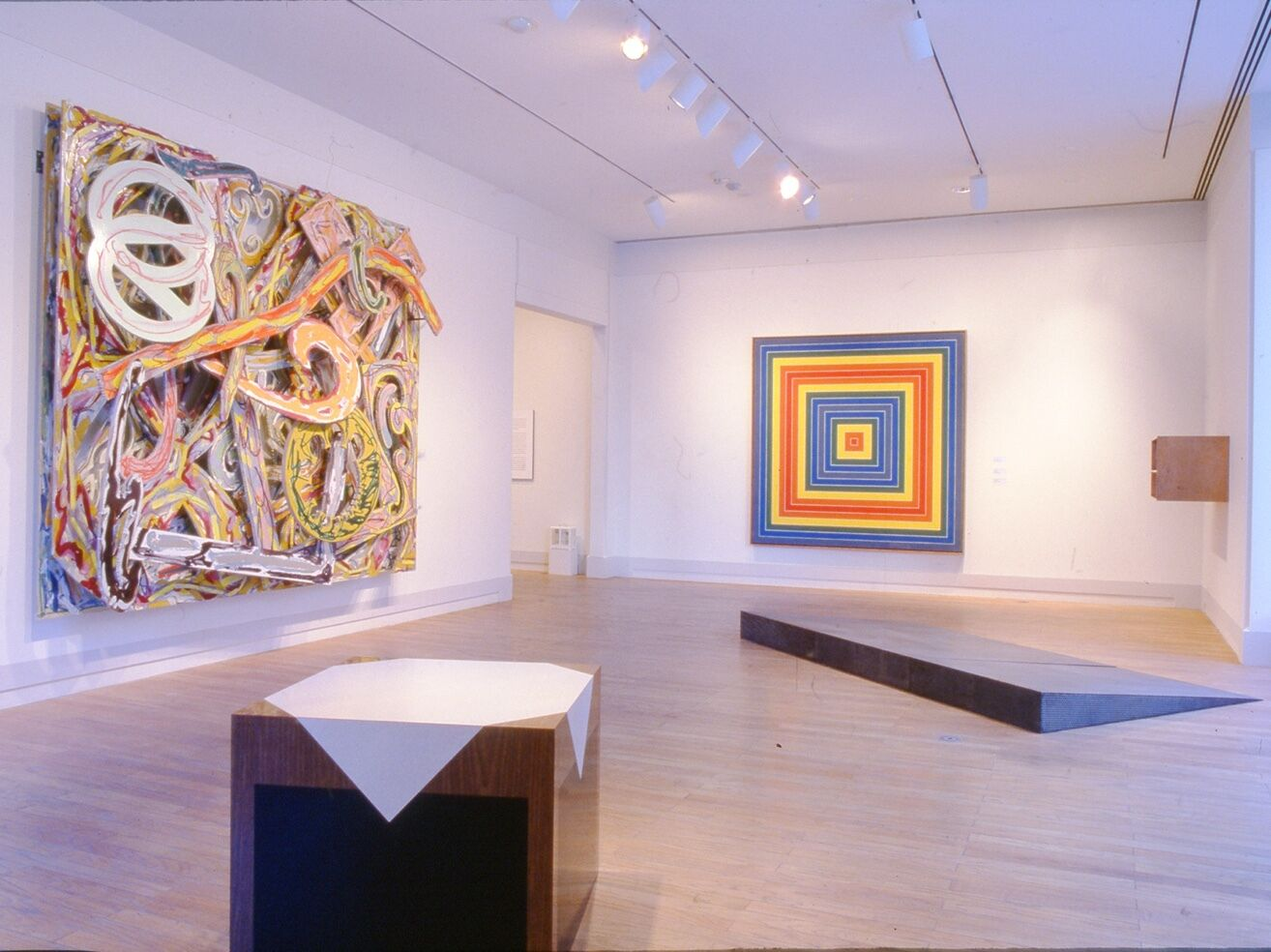 A gallery room with several pieces mounted on the wall and situated on the floor.