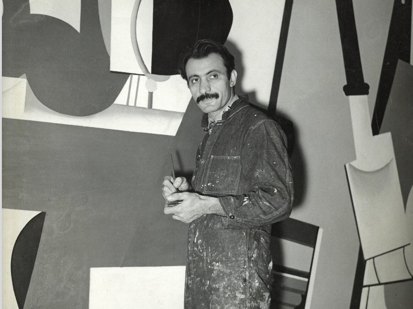 Painter Arshile Gorky standing in front of a mural.