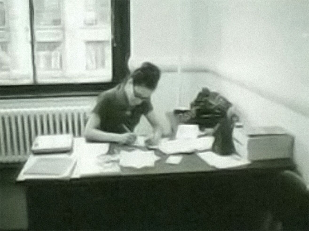 A woman sitting at a desk and looking down at a piece of paper she's writing on.