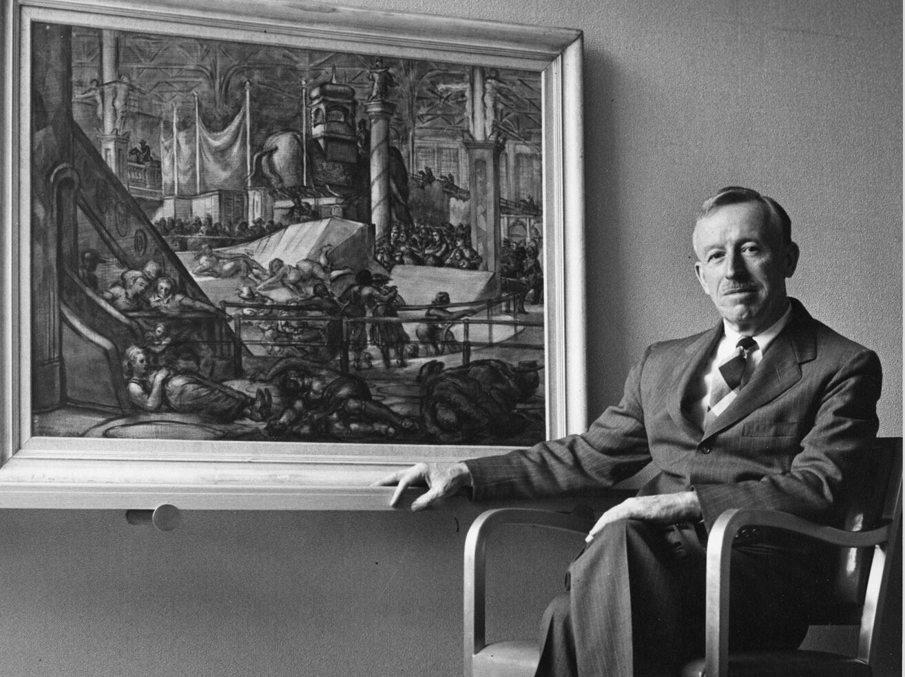 A man sits on a chair in front of a large, framed painting.
