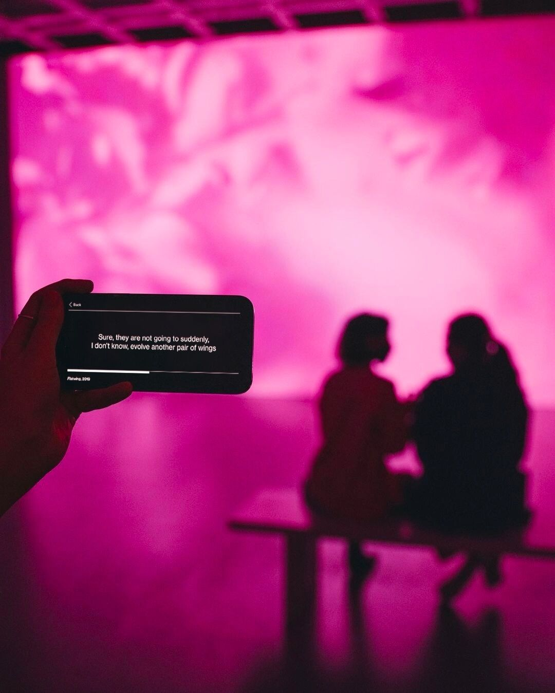 In the foreground, a hand holds a mobile device displaying white words on a black background and in the background, a two people view a fuchsia-soaked projection on a wall.