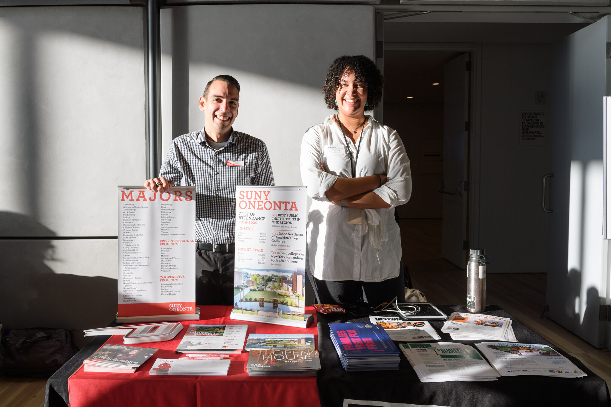 Two people stand behind a table full of college marketing materials.