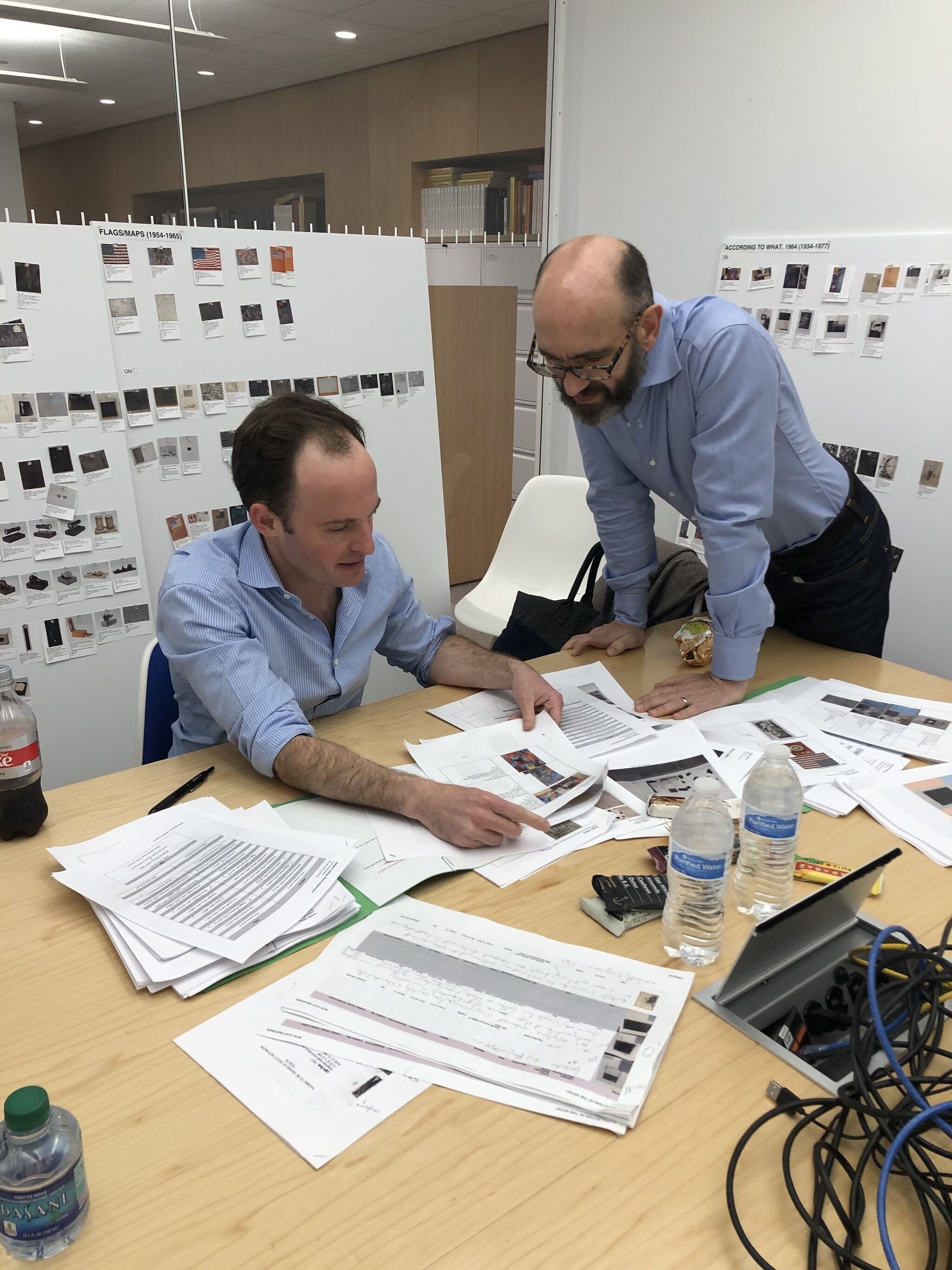Curators Scott Rothkopf and Carlos Basualdo, both wearing blue button-down shirts, lean over a table with scattered papers related to the exhibition Jasper Johns: Mind/Mirror.