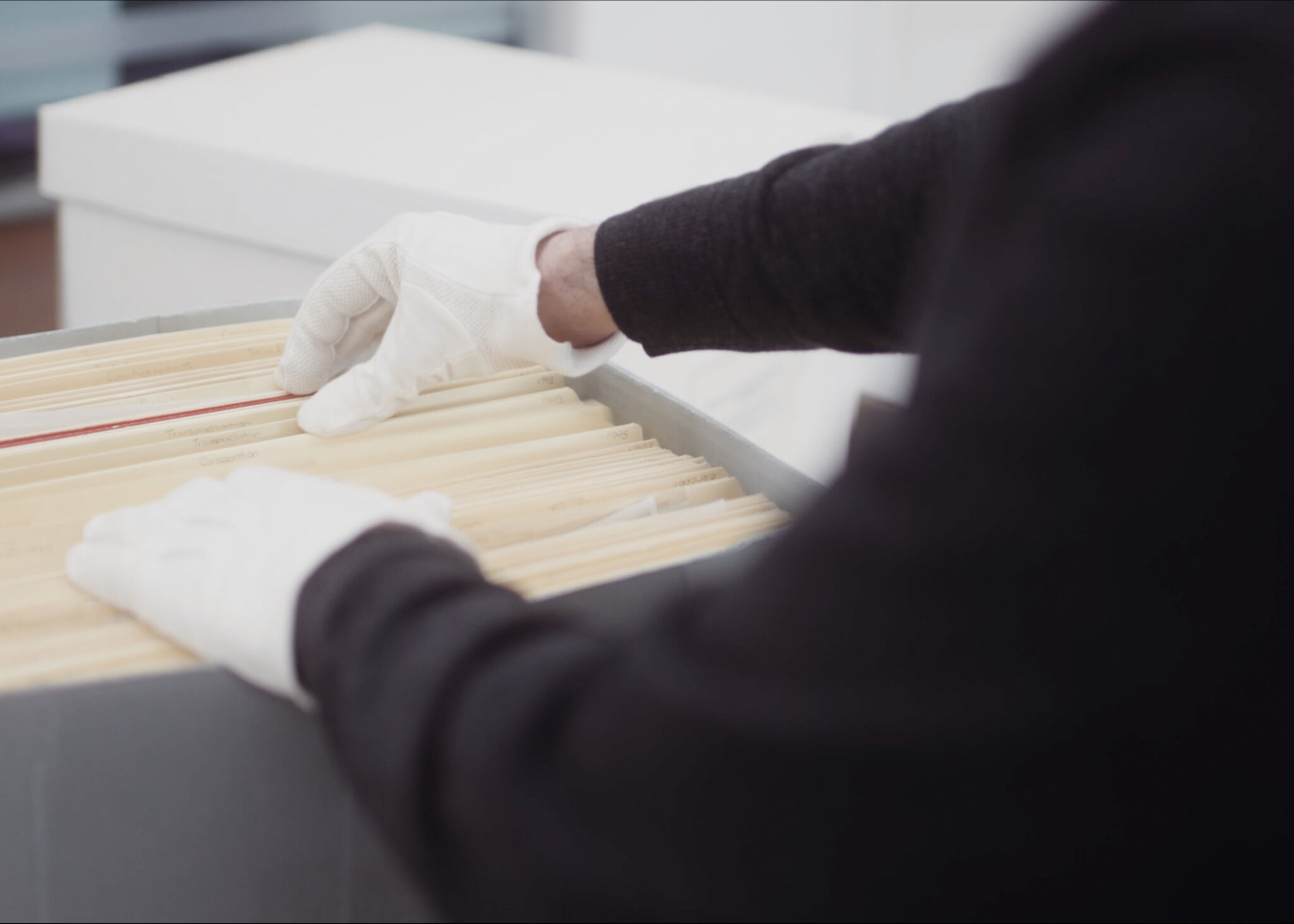 Gloved hands reaching into a box of files.