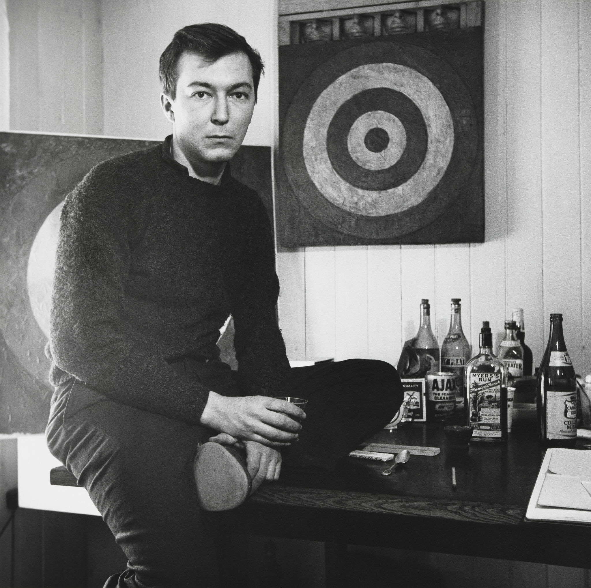 A young man sitting on the edge of a desk, looking at the viewer with a neutral expression, and holding a glass, against a backdrop of a painting on the wall and a collection of liquor bottles.